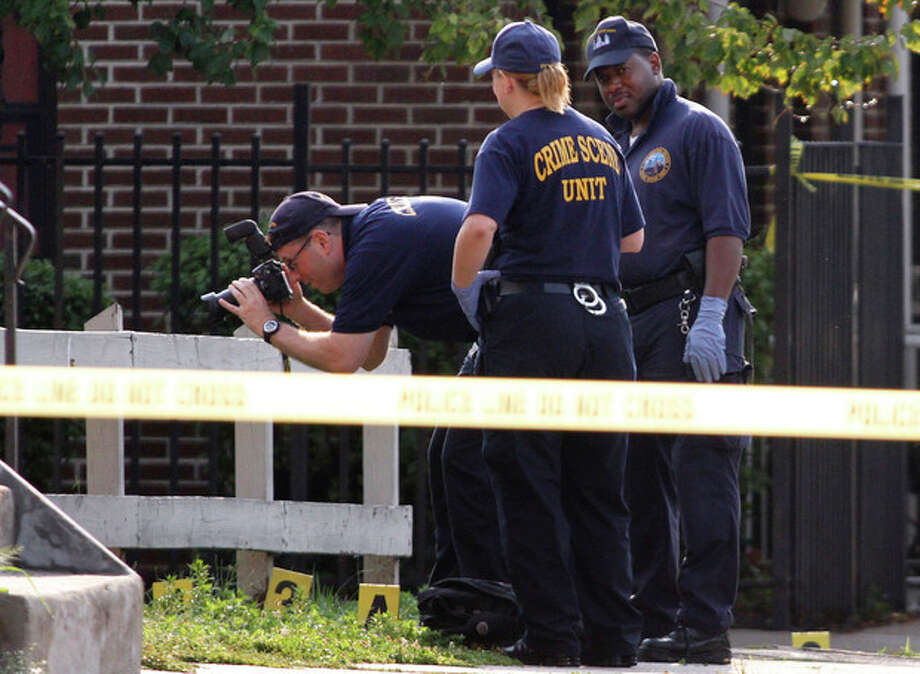 Police investigate the crime scene after an off-duty Philadelphia police officer was shot and killed, Saturday, Aug. 18, 2012, in North Philadelphia. Police said the officer had just gotten off his overnight shift and was not wearing his uniform as he walked along Cecil B. Moore Avenue, where he was shot multiple times just before 6 a.m., Saturday. The officer later died at the hospital. (AP Photo/Joseph Kaczmarek) / FR109827 AP