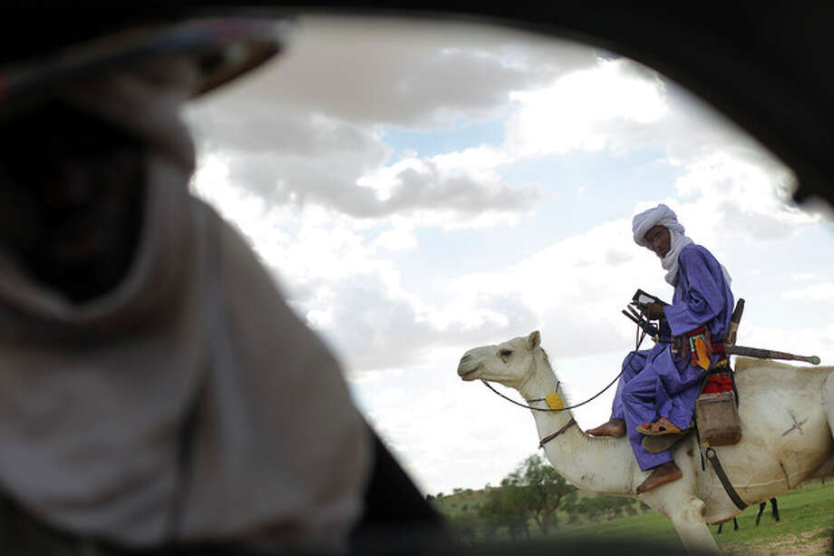 In this picture taken Tuesday July 17, 2012, a Tuareg nomad, carrying his traditional sword, rides his camel as he leaves the livestock market in Bermo, Niger, 200 kms (125 miles) north of Maradi. This is a region where it is in livestock that a man settles disputes, pays the dowry for his future bride and leaves inheritance to his sons. For generations, nomads have lived in a precarious equilibrium with the sky above them. When the first rains come, they head north toward the Sahara desert, where the grass is said to be saltier, packed with minerals. They time their movements according to the clouds, waiting for the second major downpour, before making a U-turn to head back to the greener south. (AP Photo/Jerome Delay) / AP