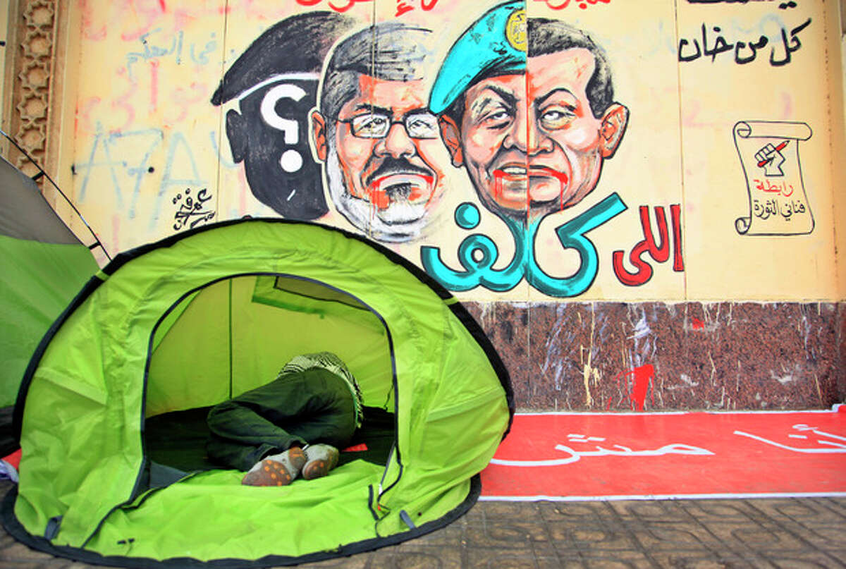 An opponent of Egypt's Islamist President Mohammed Morsi sleeps in a tent next to a wall graffiti with Arabic writing reads who assigned you did not die