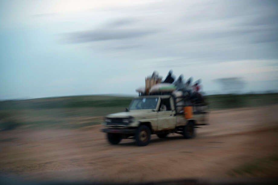 In this picture taken Monday July 16, 2012, a rare vehicle is seen carrying villagers back to Bermo, Niger, 200 kms (125 miles) north of Maradi. For generations, nomads have lived in a precarious equilibrium with the sky above them. When the first rains come, they head north toward the Sahara desert, where the grass is said to be saltier, packed with minerals. They time their movements according to the clouds, waiting for the second major downpour, before making a U-turn to head back to the greener south. If they miscalculate, they can end up stranded. As the grass turns yellow, their animals become too weak to walk. (AP Photo/Jerome Delay) / AP