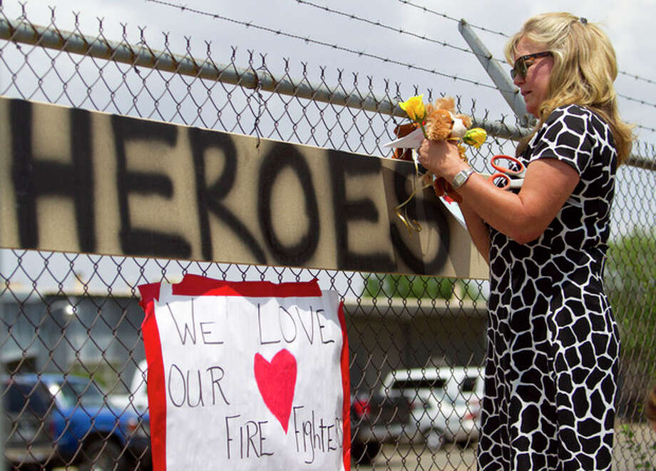Maggie Greenwood adds flowers to a makeshift memorial at the fire station Monday, July 1, 2013, in Prescott, Ariz., where an elite team of firefighters was based. Nineteen of the 20 members of the team were killed Sunday when a wildfire suddenly swept toward them in Yarnell, Ariz. (AP Photo/The Arizona Republic, David Wallace) / The Arizona Republic