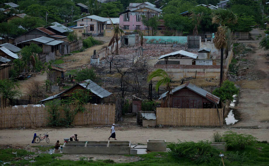 AP Photo/Gemunu AmarasingheIn this May 25 photo, Buddhist women wash clothes at a roadside common well in the foreground of ruins of the Mingalar Zayone Islamic Boarding School and its green boundary wall, background in Mingalar Zayone neighborhood, Meikhtila. / AP
