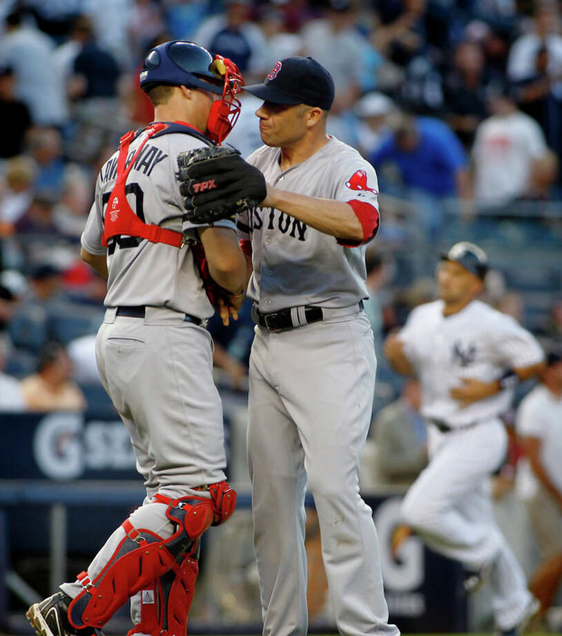 Boston Red Sox's Ryan Lavarnway (60) congratulates pitcher Alfredo Aceves, right, after he closed out the New York Yankees in the ninth inning of a baseball game, Saturday, Aug. 18, 2012, at Yankee Stadium in New York. The Red Sox defeated the Yankees 4-1. (AP Photo/John Dunn) / FR168018 AP