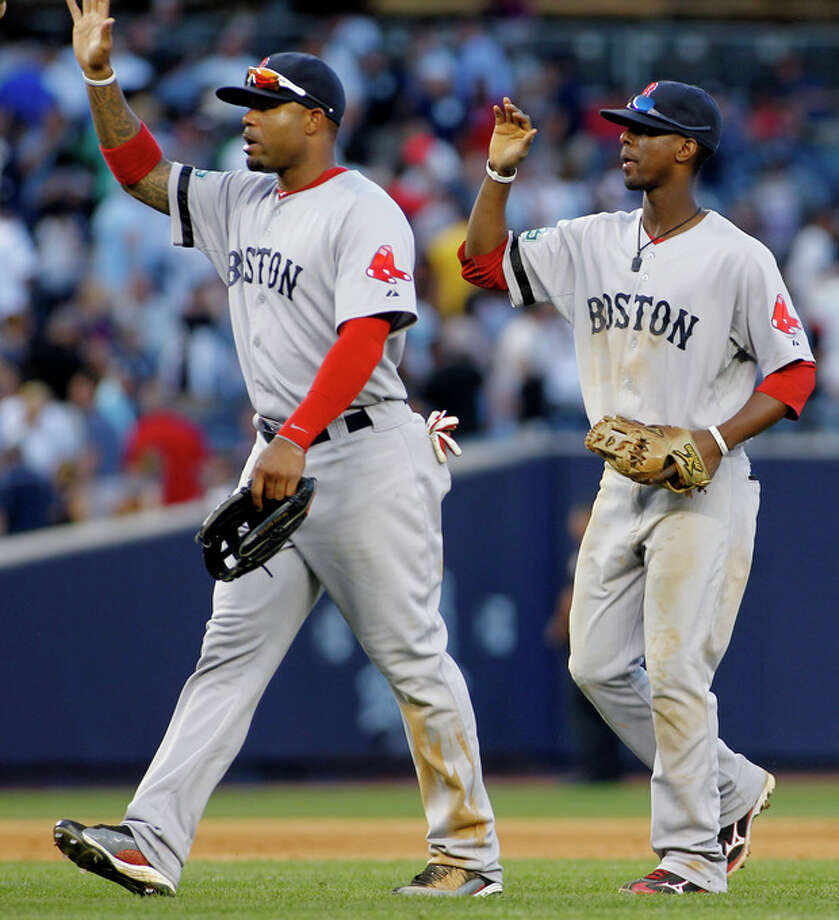 Boston Red Sox's Carl Crawford (13) and Pedro Ciriaco (77) celebrate Boston's 4-1 win over the New York Yankees in a baseball game, Saturday, Aug. 18, 2012, at Yankee Stadium in New York. (AP Photo/John Dunn) / FR168018 AP
