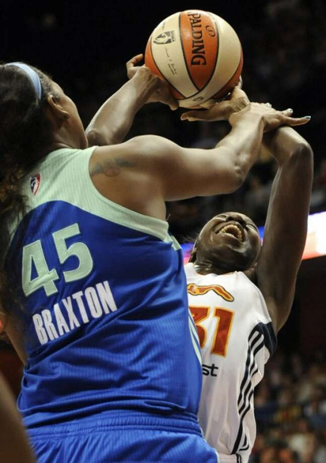 Connecticut Sun's Tina Charles, right, is fouled by New York Liberty's Kara Braxton (45) during the first half of a WNBA basketball game in Uncasville, Conn., Saturday, Aug. 18, 2012. (AP Photo/Jessica Hill)