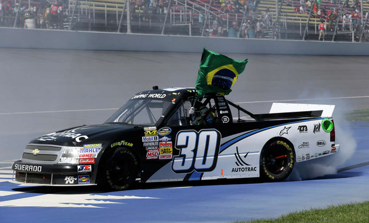 Nelson Piquet Jr. holds the Brazilian flag while celebrating after winning the NASCAR Camping World truck series VFW 200 auto race at Michigan International Speedway Saturday, Aug. 18, 2012, in Brooklyn, Mich. (AP Photo/Paul Sancya)