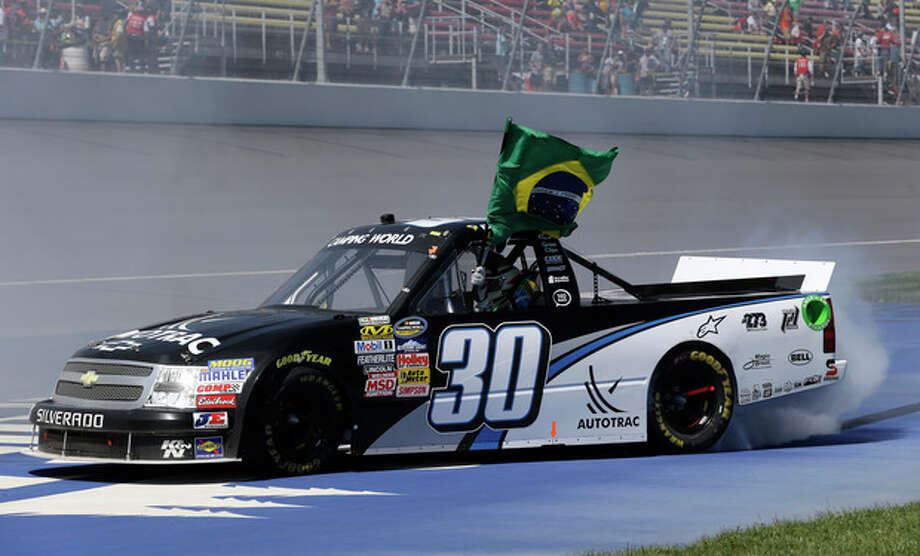 Nelson Piquet Jr. holds the Brazilian flag while celebrating after winning the NASCAR Camping World truck series VFW 200 auto race at Michigan International Speedway Saturday, Aug. 18, 2012, in Brooklyn, Mich. (AP Photo/Paul Sancya) / AP