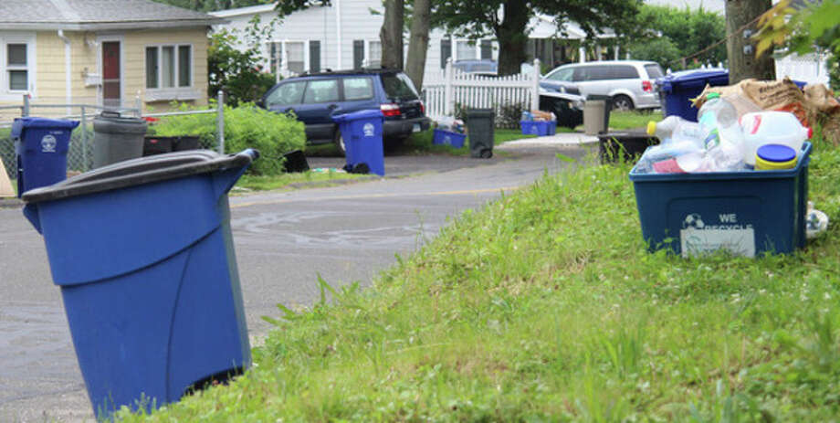 Hour photo / Chris BosakMonday was the first day for single-stream recycling in Norwalk. Streets in the Spring Hill area of the city were lined with both the new large blue recycling bins as well as the old smaller bins.