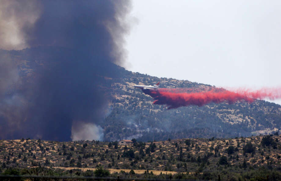 An aerial tanker drops fire retardant on a wildfires threatening homes near Yarnell, Ariz., Monday, July 1, 2013. An elite crew of firefighters was overtaken by the out-of-control blaze on Sunday, killing 19 members as they tried to protect themselves from the flames under fire-resistant shields. (AP Photo/Chris Carlson) / AP