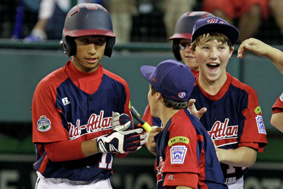 Parsippany, NJ.'s Emil Matti, left, is greeted by teammates after hitting a solo-home run off Gresham, Ore. pitcher Brett Falkner in the second inning of an elimination baseball game at the Little League World Series tournament in South Williamsport, Pa., Saturday, Aug. 18, 2012. It was Matti's second homer of the game. (AP Photo/Gene J. Puskar) / AP