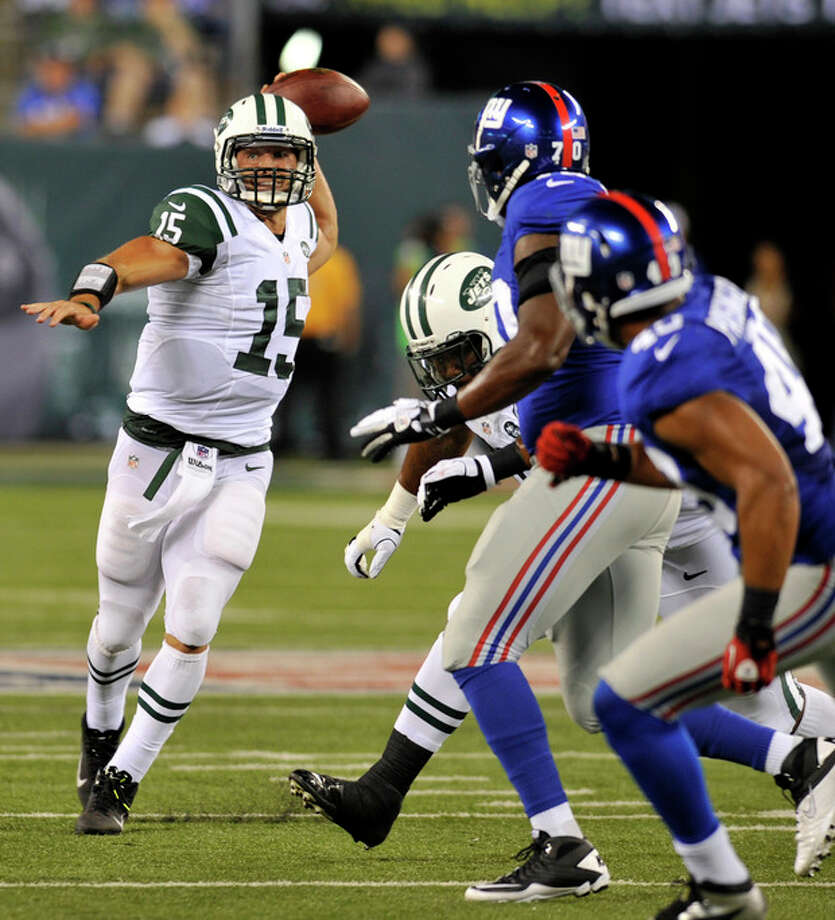 New York Jets quarterback Tim Tebow,left, looks to throw past New York Giants defenders during the second half of a preseason NFL football, Saturday, Aug. 18, 2012, in East Rutherford, N.J. (AP Photo/Bill Kostroun) / FR51951 AP