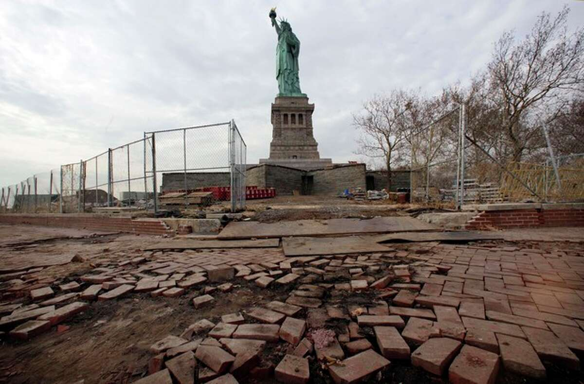 FILE - In a Nov. 30, 2012 file photo, parts of the brick walkway of Liberty Island that were damaged in Superstorm Sandy are shown during a tour of New York?'s Liberty Island. After hundreds of National Park Service workers from as far away as California and Alaska spent weeks cleaning and making repairs, the island will reopen to the public on Independence Day, July 4, 2013. (AP Photo/Richard Drew, File)