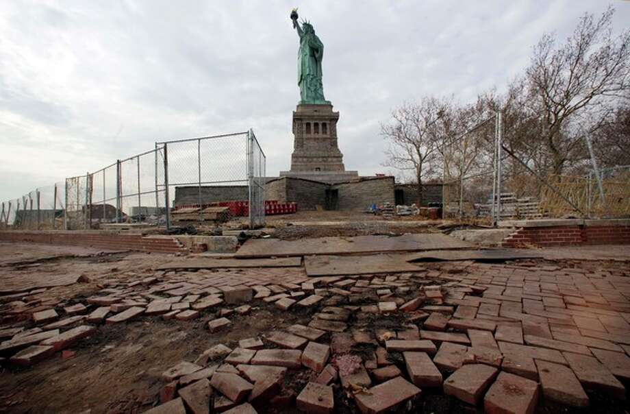 FILE - In a Nov. 30, 2012 file photo, parts of the brick walkway of Liberty Island that were damaged in Superstorm Sandy are shown during a tour of New York's Liberty Island. After hundreds of National Park Service workers from as far away as California and Alaska spent weeks cleaning and making repairs, the island will reopen to the public on Independence Day, July 4, 2013. (AP Photo/Richard Drew, File) / AP