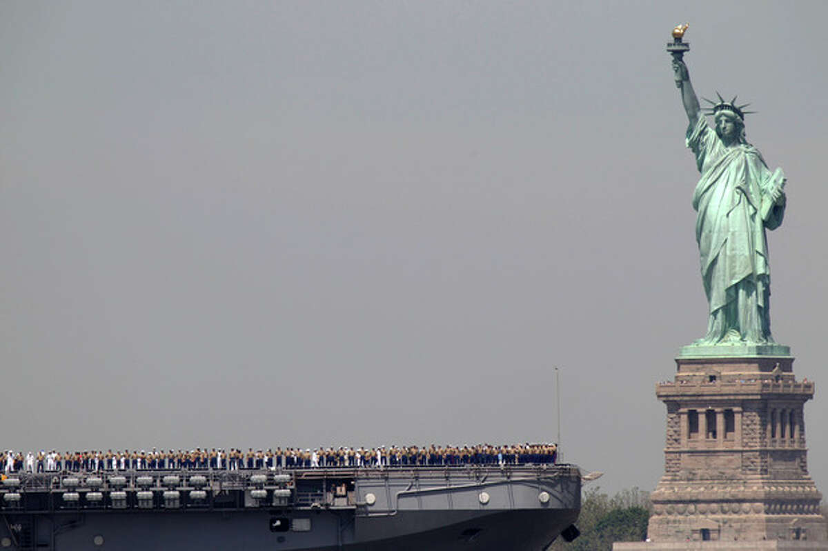 FILE - In this May 25, 2011 file photo, sailors stand on deck of the USS Iwo Jima as it passes Liberty Island and the Statue of Liberty during Fleet Week in New York. After hundreds of National Park Service workers from as far away as California and Alaska spent weeks cleaning and making repairs on the national landmark in the wake of Superstorm Sandy, Liberty Island is scheduled to reopen to the public on Independence Day, July 4, 2013. (AP Photo/Seth Wenig, File)