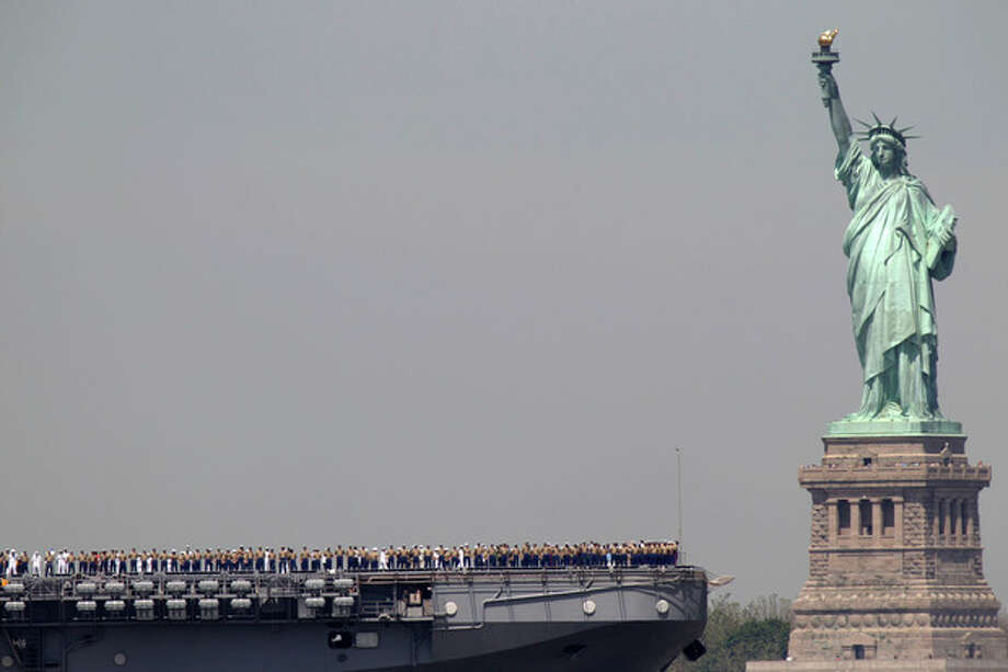 FILE - In this May 25, 2011 file photo, sailors stand on deck of the USS Iwo Jima as it passes Liberty Island and the Statue of Liberty during Fleet Week in New York. After hundreds of National Park Service workers from as far away as California and Alaska spent weeks cleaning and making repairs on the national landmark in the wake of Superstorm Sandy, Liberty Island is scheduled to reopen to the public on Independence Day, July 4, 2013. (AP Photo/Seth Wenig, File) / AP