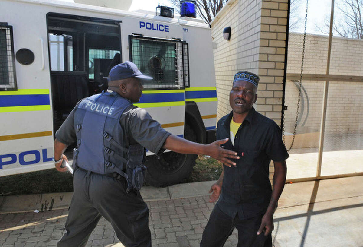 Chris Mahlangu, right, is led away from the court in Ventersdorp, South Africa, Wednesday, Aug. 22, 2012 after receiving a life sentence for the murder of right wing leader Eugene TerreBlanche. A black farmworker was sentenced to life in prison Wednesday for the brutal murder of South African white supremacist leader Eugene Terreblanche in a case that has been a source of racial tension in the city of Ventersdorp. Mahlangu was found guilty for beating Terreblanche, 69, to death with an iron in April 2010. (AP Photo) SOUTH AFRICA OUT