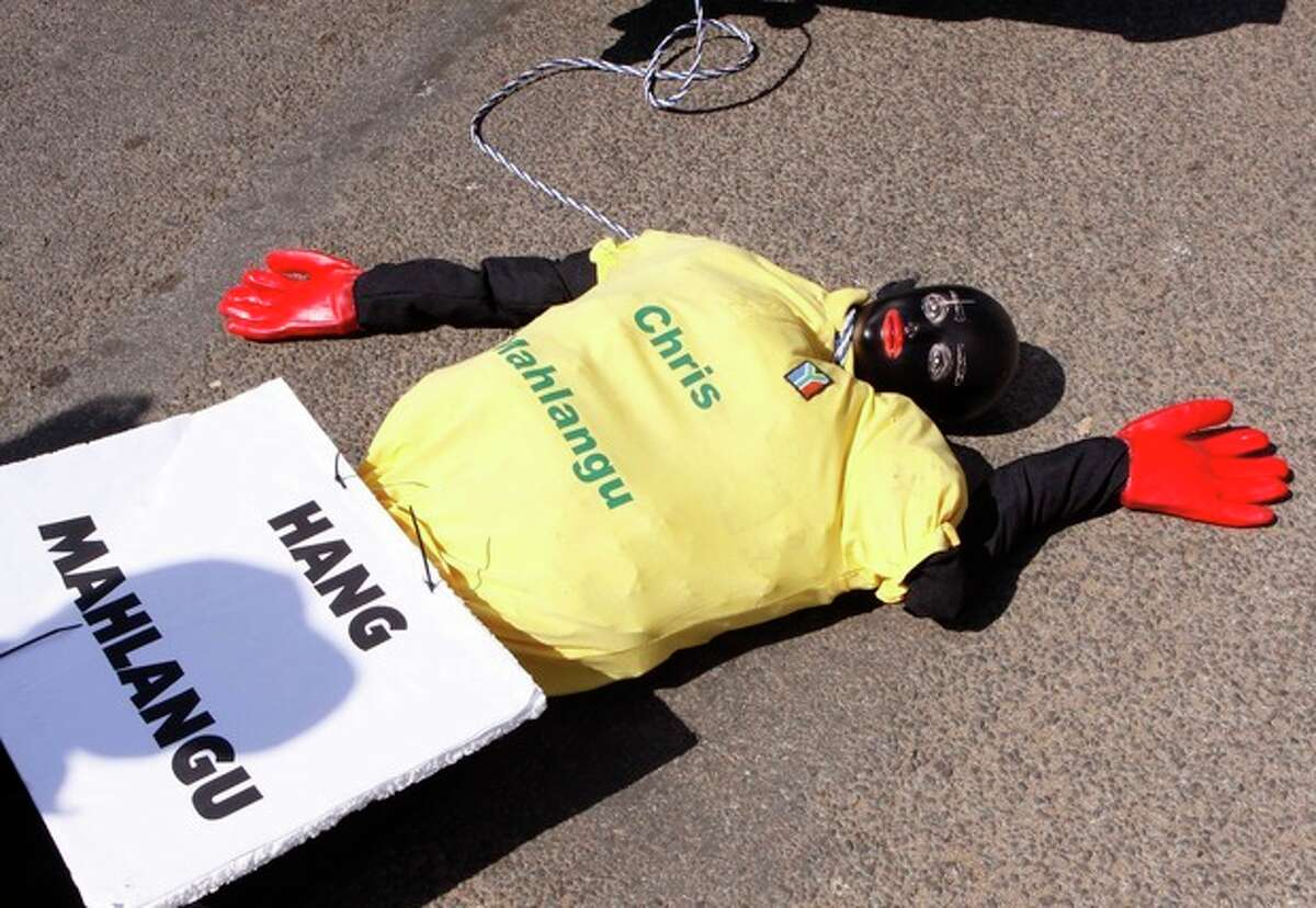 An effigy of the killer of right wing leader Eugene TerreBlanche is prepared to be dragged behind a vehicle outside the court in Ventersdorp, South Africa, Wednesday Aug. 22 2012. Chris Mahlangu was given a life sentence for the 2010 murder of TerreBlanche. (AP Photo/Denis Farrell)