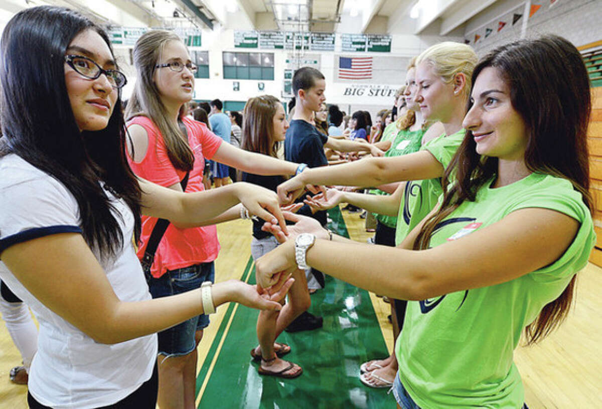 85 members of this year's Norwalk High School senior class including Efthimia Kutrudis, right, participated in a orientation program with over 140 incoming freshman like Rachel Helisch as part of the new Link Crew program at the school. The program has seniors mentor and guide freshmen to be successful during the transition to high school and help facilitate freshman success. Hour photo / Erik Trautmann