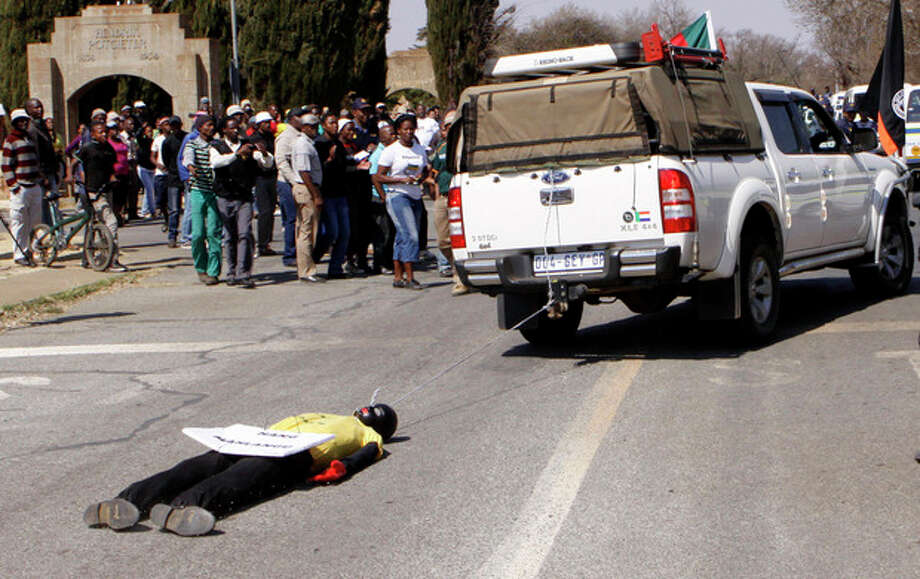 "An effigy of the killer of right wing leader Eugene TerreBlanche is dragged behind a vehicle past protesters outside the court in Ventersdorp, South Africa, Wednesday Aug. 22 2012. A black farmworker was sentenced to life in prison Wednesday for the brutal murder of South African white supremacist leader Eugene Terreblanche in a case that has been a source of racial tension in the city of Ventersdorp. About 100 protesters sang anti-white songs outside the courtroom in the city just west of Johannesburg to support 30-year-old Chris Mahlangu, who had pleaded guilty but argued that he acted in self-defense in what the judge found was a violent dispute over wages. They were opposed by 20 white protesters who carried the doll of a black man with a rope around his neck and a sign that said: ""Hang Mahlangu."" (AP Photo/Denis Farrell) / AP"