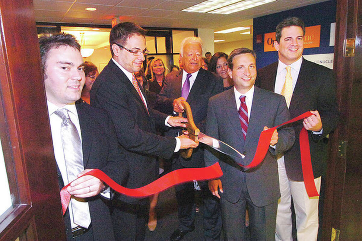 Hour Photo/ Alex von Kleydorff David Lewis, president and CEO of OperationsInc., helps Norwalk Mayor Richard Moccia, State Sen. Bob Duff, and State Rep. Chris Perone cut the ribbon on the firm's new office space at 535 Connecticut Ave.