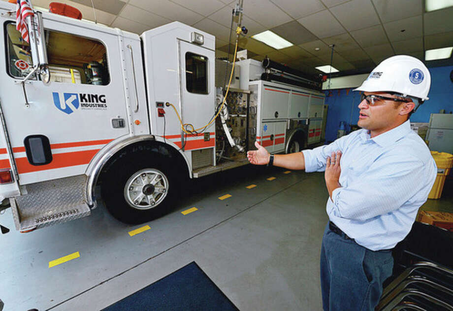 Hour photo / Erik TrautmannBob King points to a fire truck used at the plant to battle blazes and assist with other safety functions. / (C)2012, The Hour Newspapers, all rights reserved