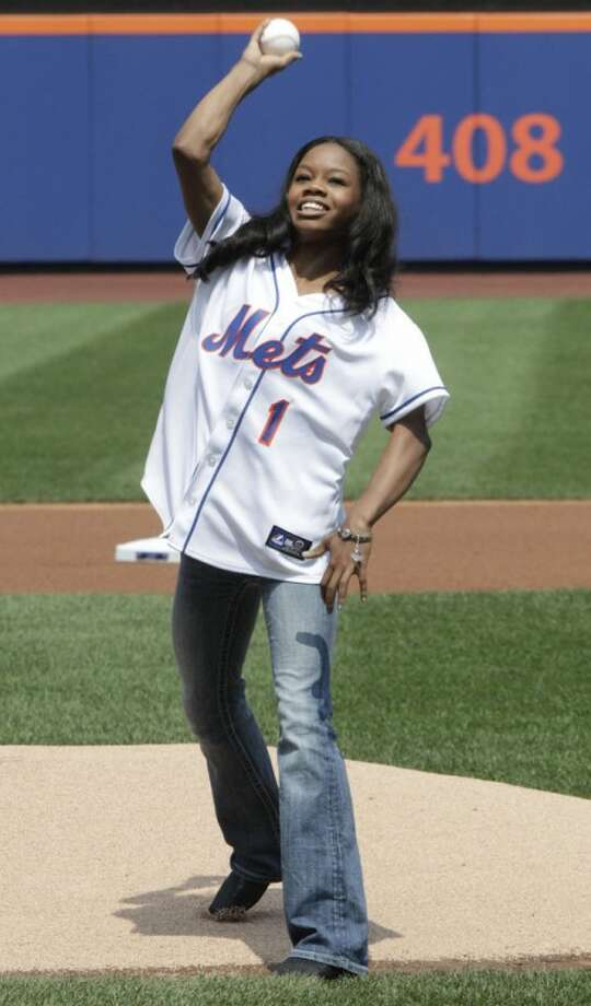 Olympic gold medal gymnast Gabrielle Douglas throws out the ceremonial first pitch before a baseball game between the New York Mets and the Colorado Rockies, Thursday, Aug. 23, 2012, in New York. (AP Photo/Frank Franklin II)