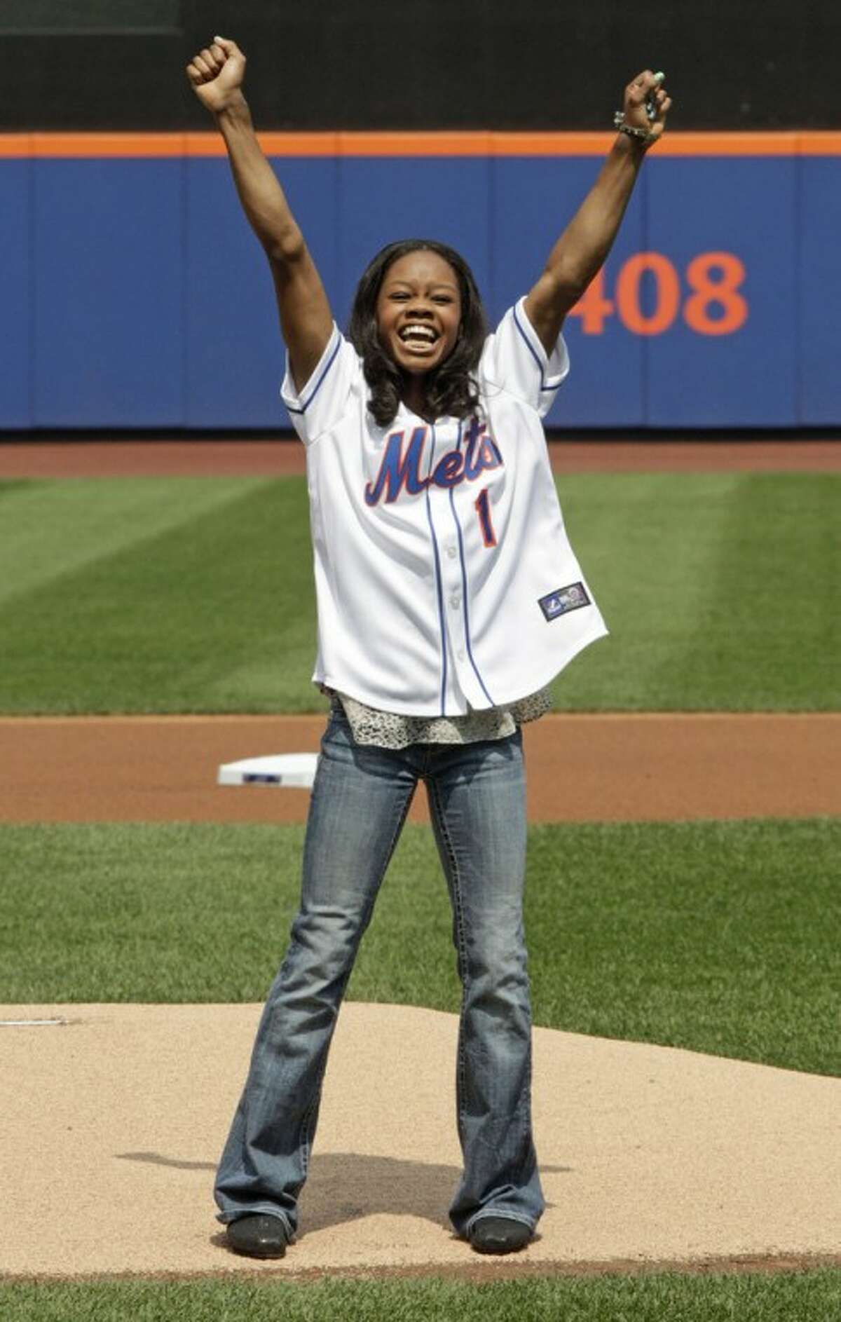 Olympic gold medal gymnast Gabrielle Douglas reacts after throwing the ceremonial first pitch before a baseball game between the New York Mets and the Colorado Rockies, Thursday, Aug. 23, 2012, in New York. (AP Photo/Frank Franklin II)