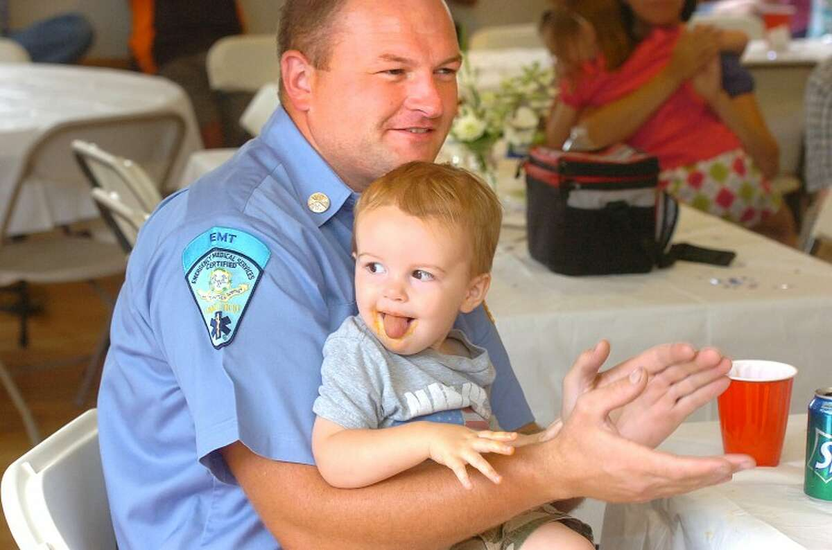 Hour Photo/ Alex von Kleydorff. Fire Fighter Dan Lewis holds son Jack in his lap during remarks about the career of fellow fire fighter Karl Dolnier at his retirement party on Sunday