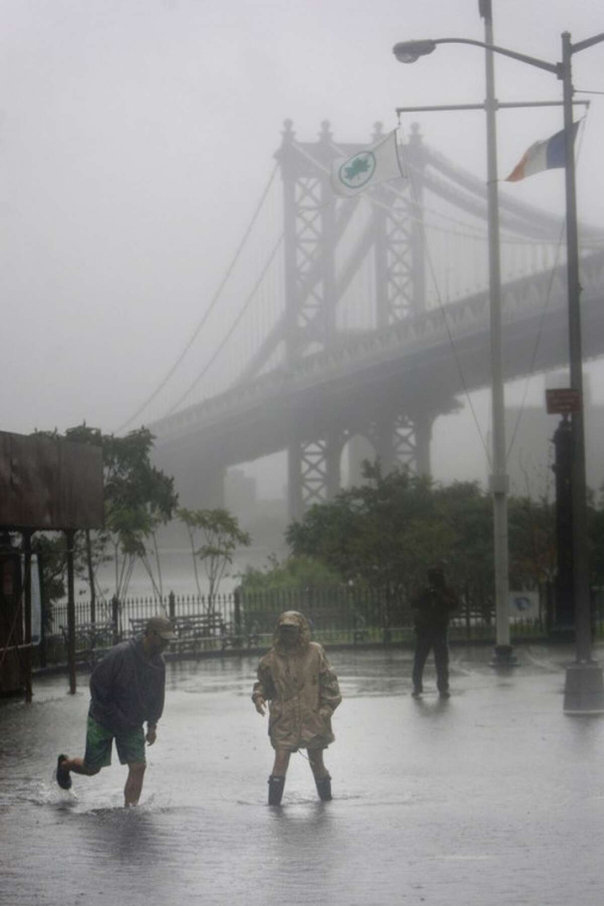 FILE - In this Aug. 28, 2011, file photo, people near New York's Brooklyn Bridge wade through floodwaters brought on by Hurricane Irene, which weakened to a tropical storm just before hitting New York's Coney Island. Two years prior to Irene, 100 scientists and engineers met to sketch out a bold defense: massive, moveable barriers to shield New York City from a storm-stirred sea. The network would protect Manhattan and parts of the four outer boroughs and New Jersey, but not some vulnerable swaths of Brooklyn and Queens. (AP Photo/Seth Wenig, File)