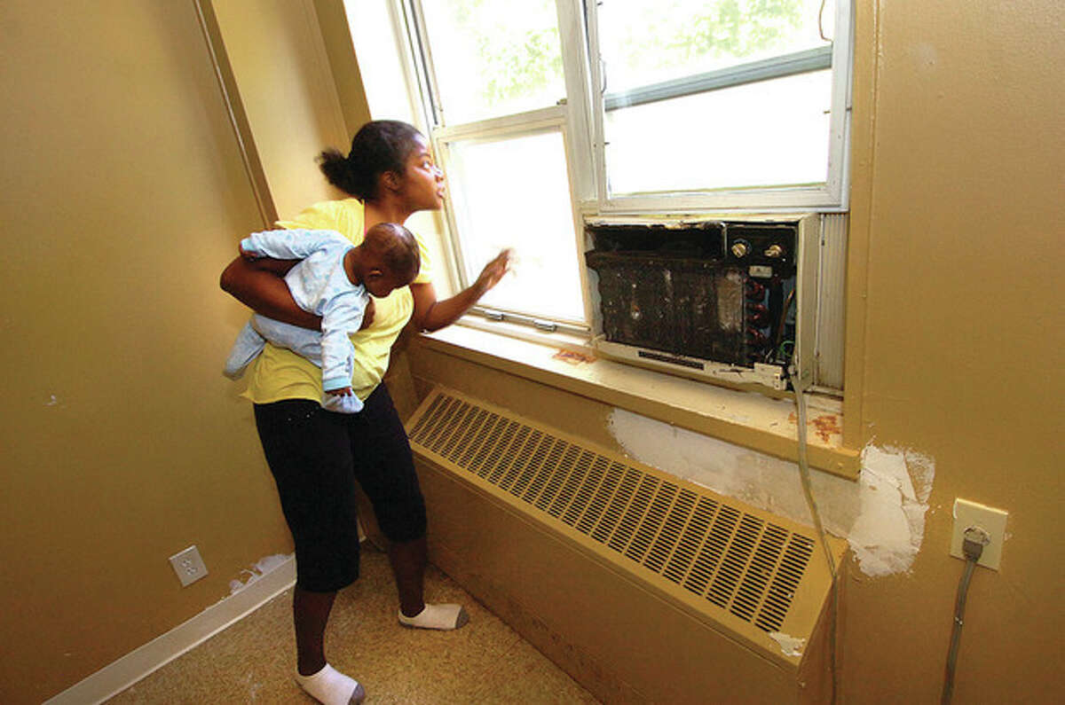 Above, Hour photo / Alex von Kleydorff Below, contributed photo Above, Shatiqua Fleming holds her 4-month-old baby, Eric, while she looks through one of the many broken windows of an apartment in Building 22 at Roodner Court. Below, the apartment in Roodner Court that Fleming is cleaning and painting before moving in.