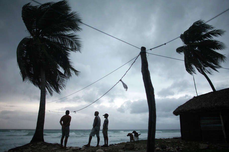 People look out at the beach as Tropical Storm Isaac approaches in Barahona, Dominican Republic, Friday, Aug. 24, 2012. Isaac strengthened slightly as it spun toward the Dominican Republic and Haiti, but seemed unlikely to gain enough steam early Friday to strike the island of Hispaniola as a hurricane. The storm's failure to gain the kind of strength in the Caribbean that forecasters initially projected made it more likely that Isaac won't become a hurricane until it enters the Gulf of Mexico, said Eric Blake, a forecaster with U.S. National Hurricane Center in Miami. (AP Photo/Ricardo Arduengo) / AP