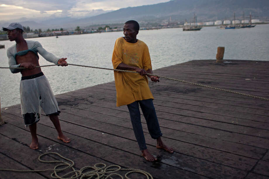 Fishermen pull on a rope in Port Cite Soleil in Port-au-Prince, Haiti, Friday, Aug. 24, 2012. Tropical Storm Isaac strengthened slightly as it spun toward the Dominican Republic and Haiti, but seemed unlikely to gain enough steam early Friday to strike as a hurricane. The storm's failure to gain the kind of strength in the Caribbean that forecasters initially projected made it more likely that Isaac won't become a hurricane until it enters the Gulf of Mexico, said Eric Blake, a forecaster with U.S. National Hurricane Center in Miami. (AP Photo/Dieu Nalio Chery) / AP
