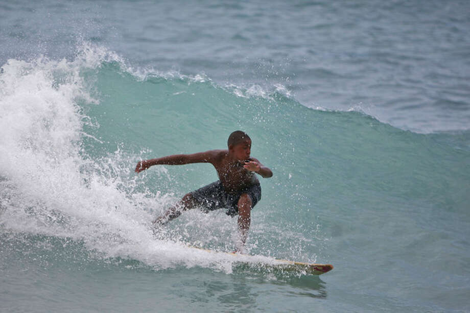 A boy surfs a wave at a beach in Barahona, Dominican Republic, before the anticipated arrival of Tropical Storm Isaac, Thursday, Aug. 23, 2012. U.S. forecasters said Isaac will likely turn into a Category 1 hurricane by Friday as it nears the Dominican Republic and Haiti. (AP Photo/Ricardo Arduengo) / AP
