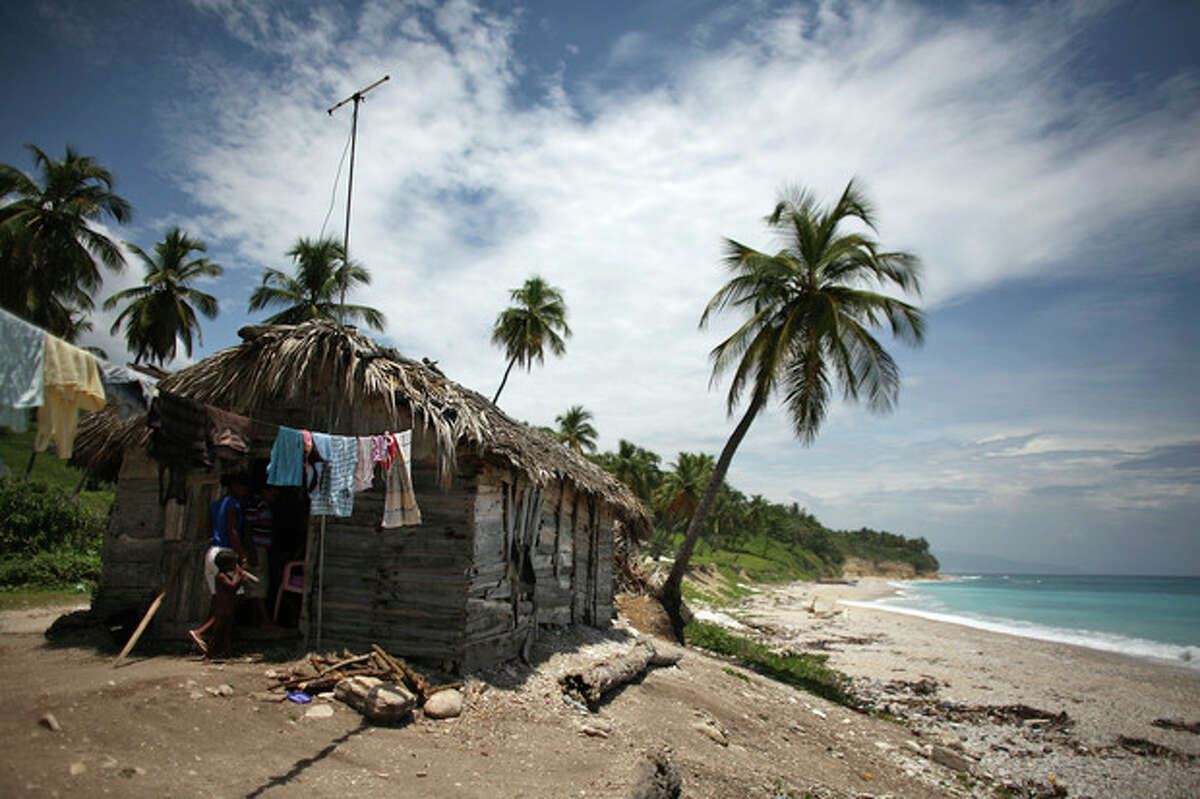 Two people walk into a thatched roof hut located along the shore in Barahona, Dominican Republic, Thursday, Aug. 23, 2012. Tropical Storm Isaac churned toward the Dominican Republic and Haiti on Thursday, threatening to strengthen into a hurricane. (AP Photo/Ricardo Arduengo)