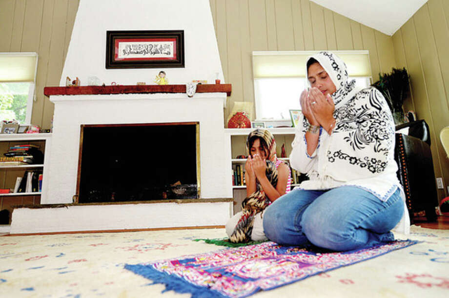Hour photo / Erik TrautmannMuslim residents Azra Asaduddin and her daughter Nuha Khan pray during the holy month of Ramadan where the faithful fast from sunrise to sundown. / (C)2013, The Hour Newspapers, all rights reserved