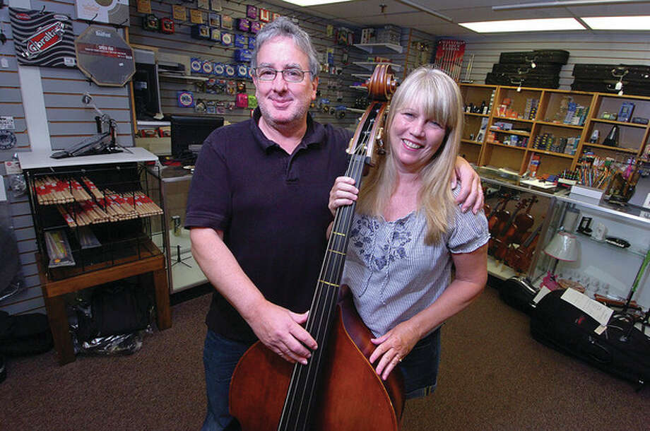Hour Photo/ Alex von KleydorffSteve Sasloe and his wife Kathy stand in their store, Westport Music, this week. They have been running the business for 30 years. Below, guitars hang on the wall of their store. / 2012 The Hour Newspapers