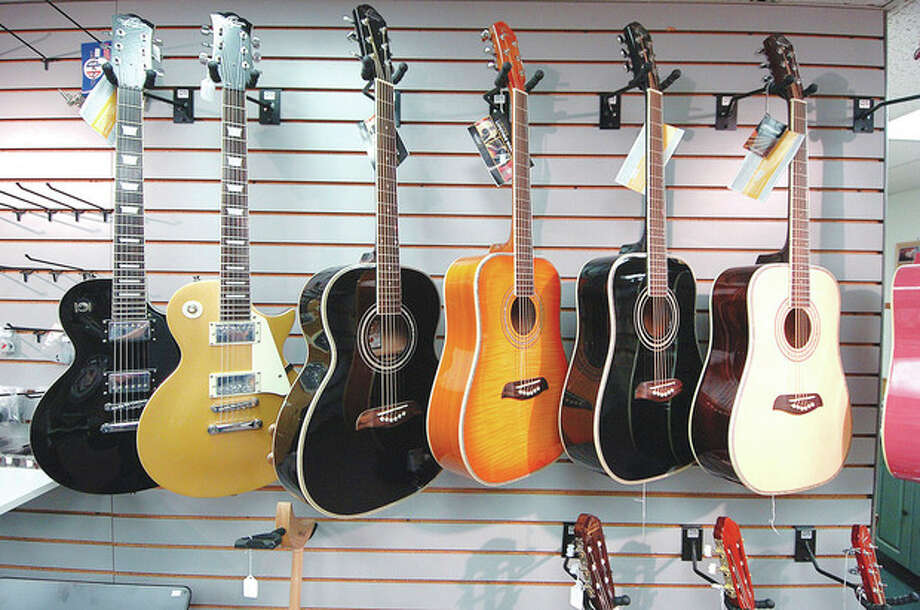Hour Photo/ Alex von Kleydorff. Guitars for sale hang in the Westport Music Center / 2012 The Hour Newspapers