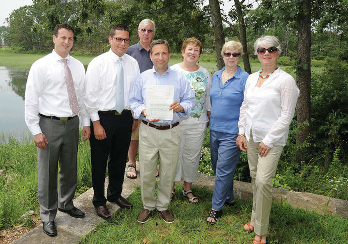 Hour photo/Matthew Vinci State Sen. Bob Duff (middle) presents a check Tuesday to the Norwalk Land Trust, from left, Vincent LaBella and Matthew Stoja with Enterprise Rent a Car, John Moeling, Duff, Midge Kennedy, Peggy Holtman and Kathy Siever.