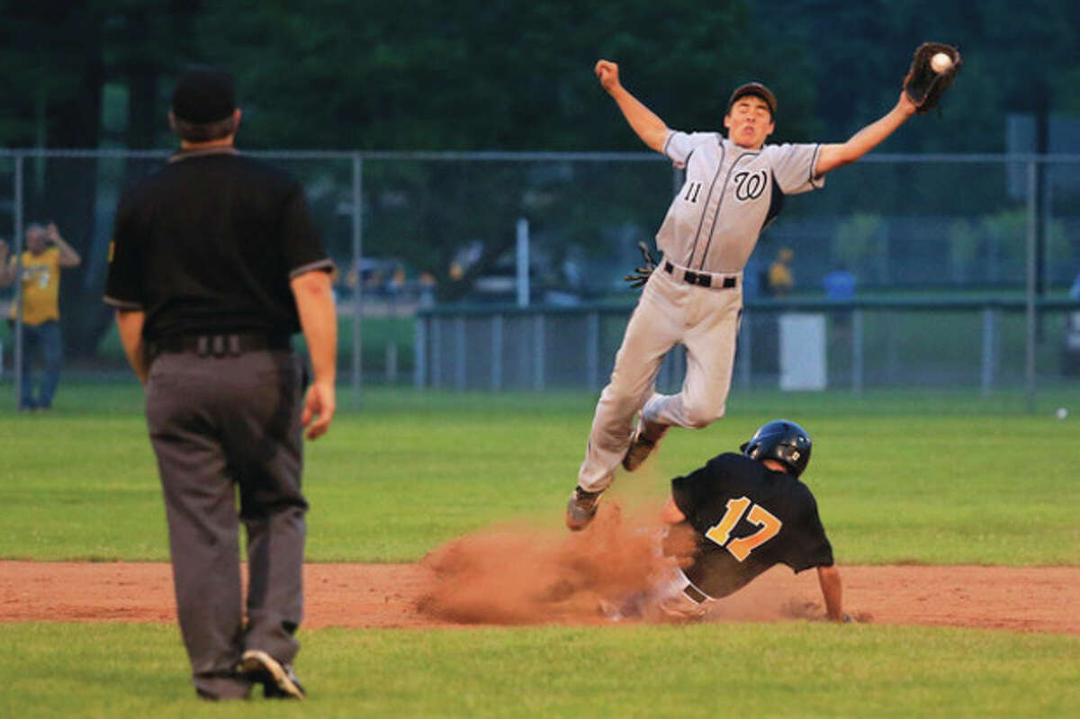 Hour photo/Chris Palermo Collin Kahal leaps to corral the ball as a Trumbull runner slides safely into second base during Tuesday night's 13-year-old Babe Ruth District I championship game at Unity Park in Trumbull. Trumbull took the title with a 5-2 victory.