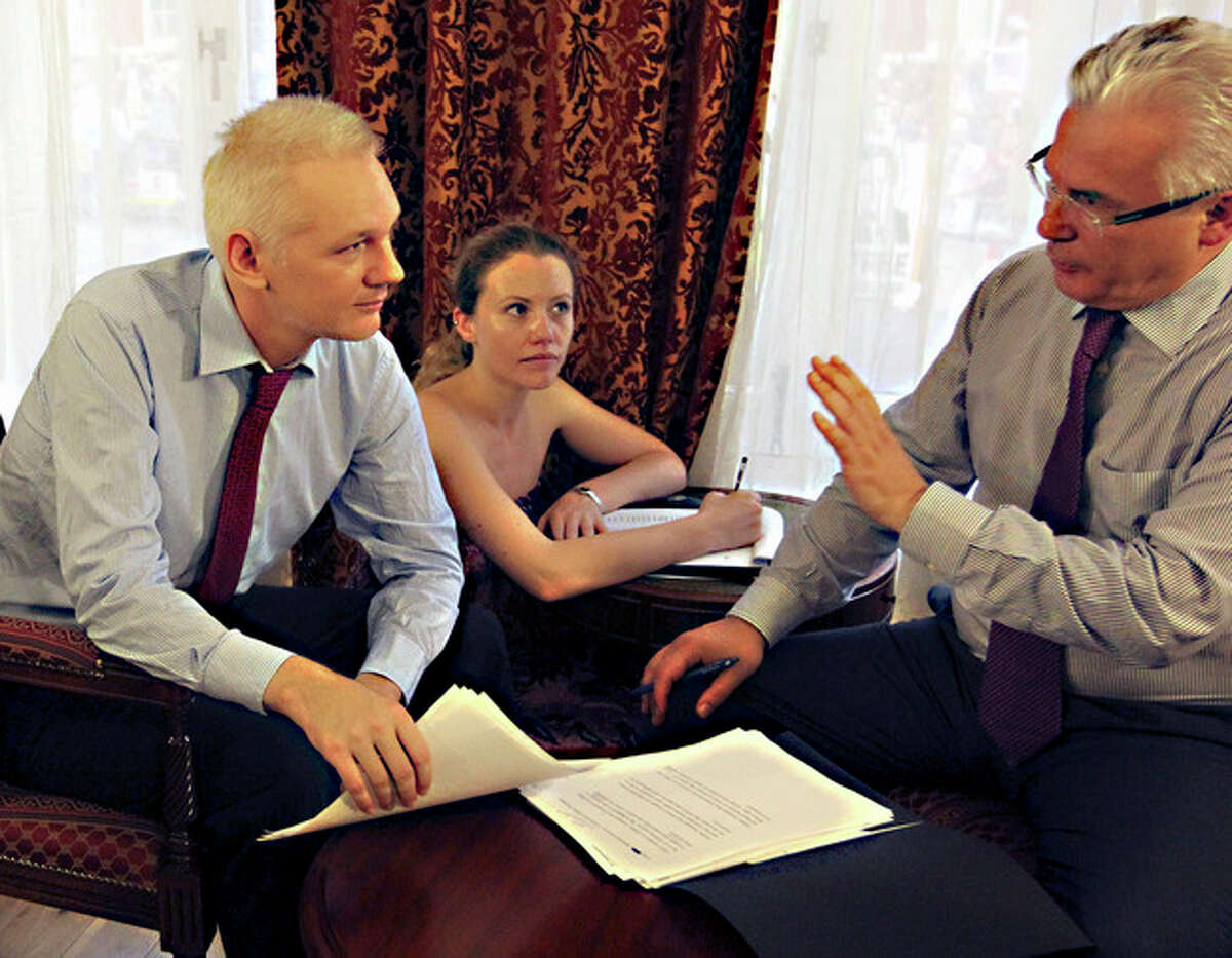 WikiLeaks founder Julian Assange, left, with his legal adviser Balthasar Garcon, right, talk inside the Ecuadorian embassy in London, Sunday Aug. 19, 2012. WikiLeaks founder Julian Assange took refuge inside Ecuador's Embassy in London two months ago, seeking to avoid extradition to Sweden for questioning over sexual misconduct allegations. Woman at centre unidentified. (AP Photo / Sean Dempsey, PA) UNITED KINGDOM OUT - NO SALES - NO ARCHIVE