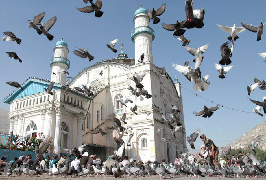 Pigeons fly outside Shah-e-Dushamshera's mosque where Afghans offer the Eid al-Fitr's prayers that marks the end of holy fasting month of Ramadan in Kabul, Afghanistan, Sunday, Aug. 19, 2012. (AP Photo/Musadeq Sadeq) / AP