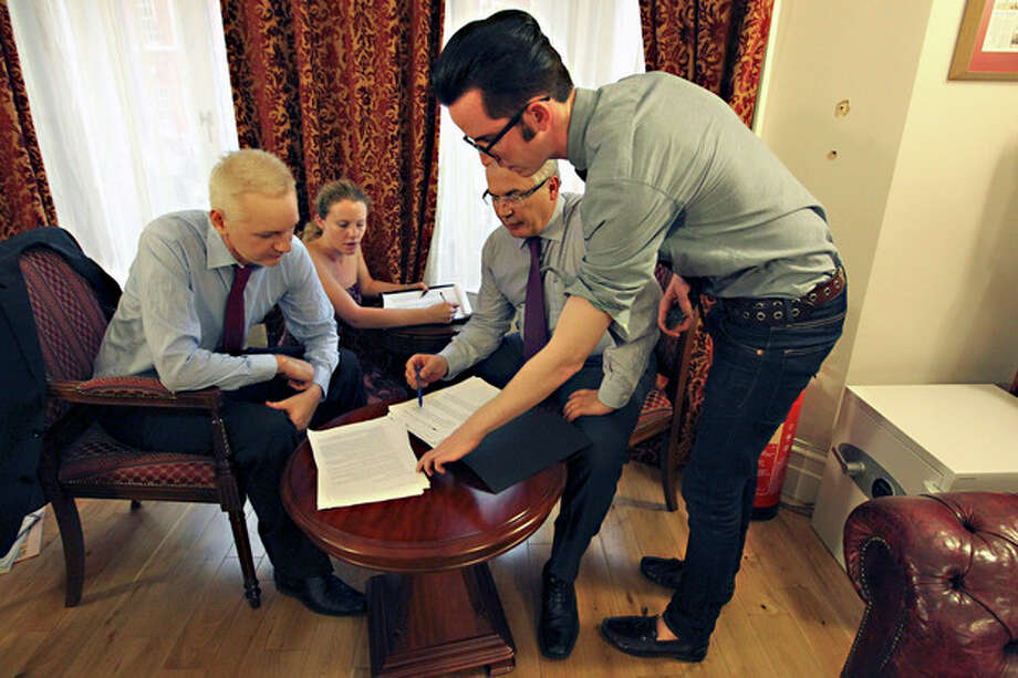WikiLeaks founder Julian Assange, left, with his legal adviser Balthasar Garcon, 2nd right, with others unidentified, look at papers inside the Ecuadorian embassy in London, Sunday Aug. 19, 2012. WikiLeaks founder Julian Assange took refuge inside Ecuador's Embassy in London two months ago, seeking to avoid extradition to Sweden for questioning over sexual misconduct allegations. (AP Photo / Sean Dempsey, PA) UNITED KINGDOM OUT - NO SALES - NO ARCHIVE / PA