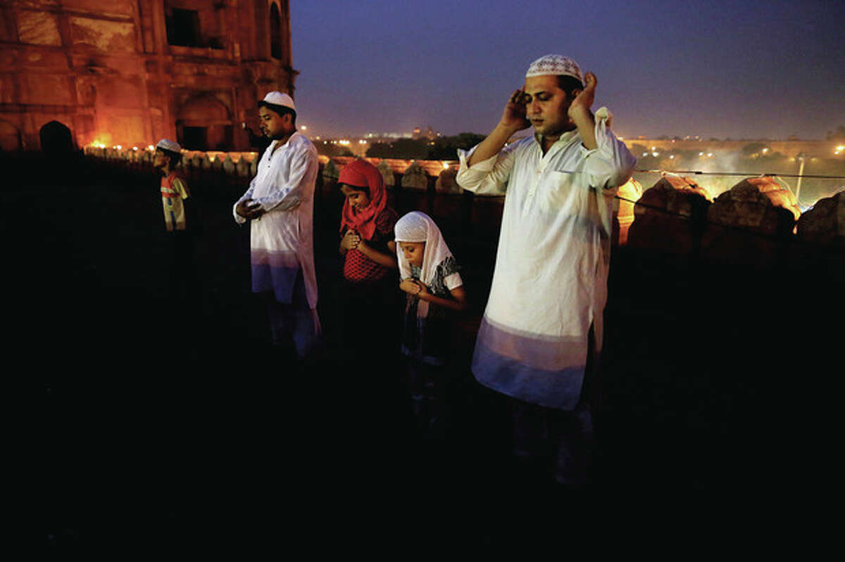 An Indian Muslim prays after breaking fast on the last day of the holy month of Ramadan before the Eid holiday, on the walls of the Jama Masjid in New Delhi, India, Sunday, Aug. 19, 2012. Muslims around the world celebrate Eid al-Fitr, marking the end of Ramadan, the Muslim calendar's ninth and holiest month during which followers are required to abstain from food and drink from dawn to dusk. (AP Photo/Kevin Frayer)