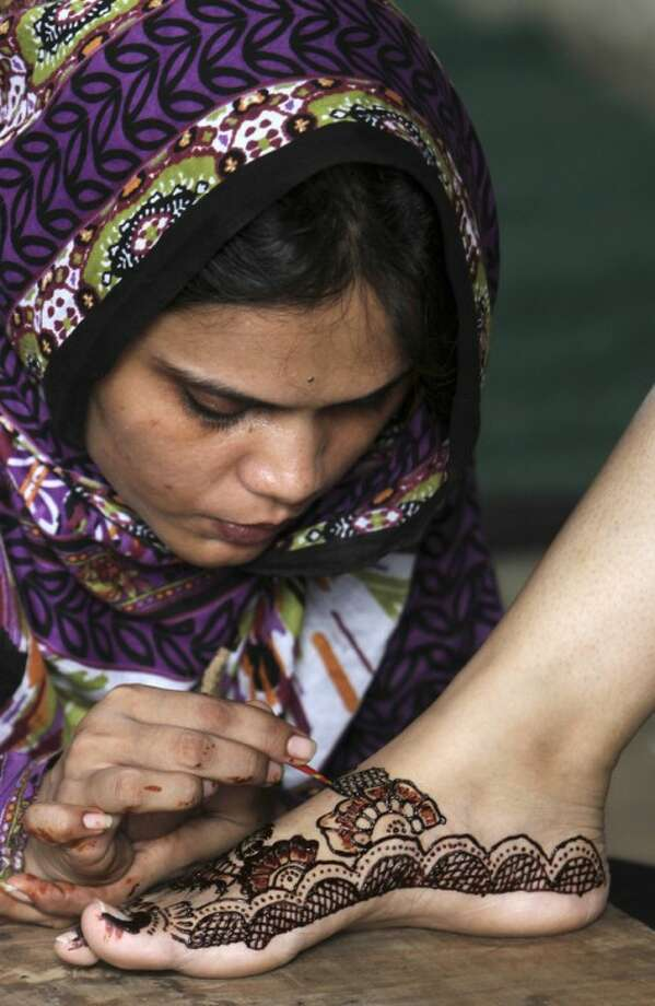 A Pakistani woman paints a customer's feet with henna in preparation for the upcoming Eid al-Fitr festival, in Karachi, Pakistan, Saturday, Aug. 18, 2012. Eid al-Fitr marks the end of the holy month of Ramadan. (AP Photo/Fareed Khan)