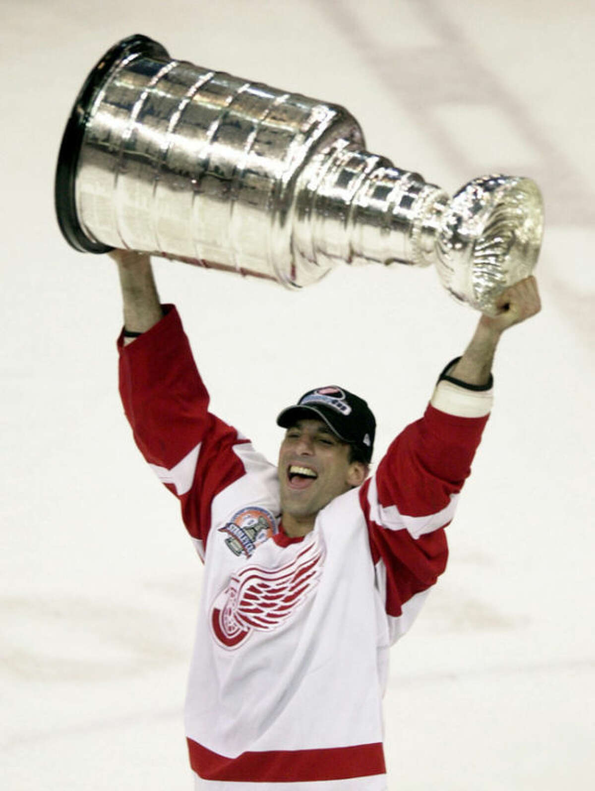 FILE - In this Jan. 8, 2008 file photo, Detroit Red Wings defenseman Chris Chelios skates with the Stanley Cup in Detroit after defeating the Carolina Hurricanes, in this June 13, 2002 file photo. Defensemen Scott Niedermayer and Chelios, along with forward Brendan Shanahan have been picked for the Hockey Hall of Fame. (AP Photo/Paul Sancya, file)