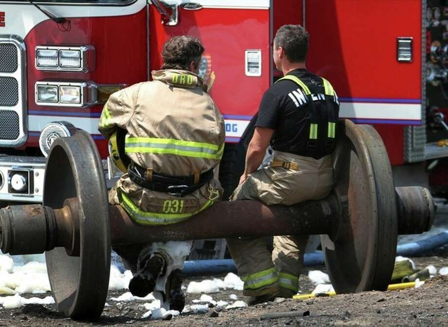 In a Sunday, July 7, 2013 photo, firefighters take a break on a set of train wheels in Lac-Megantic, Quebec, in a Surete du Quebec handout photo made available Tuesday, July 9, 2013. Thirteen people are confirmed dead and forty more are listed as missing after a train derailed ignited tanker cars carrying crude oil. (AP Photo/Surete du Quebec via The Canadian Press) / Surete du Quebec via The Canadian Press
