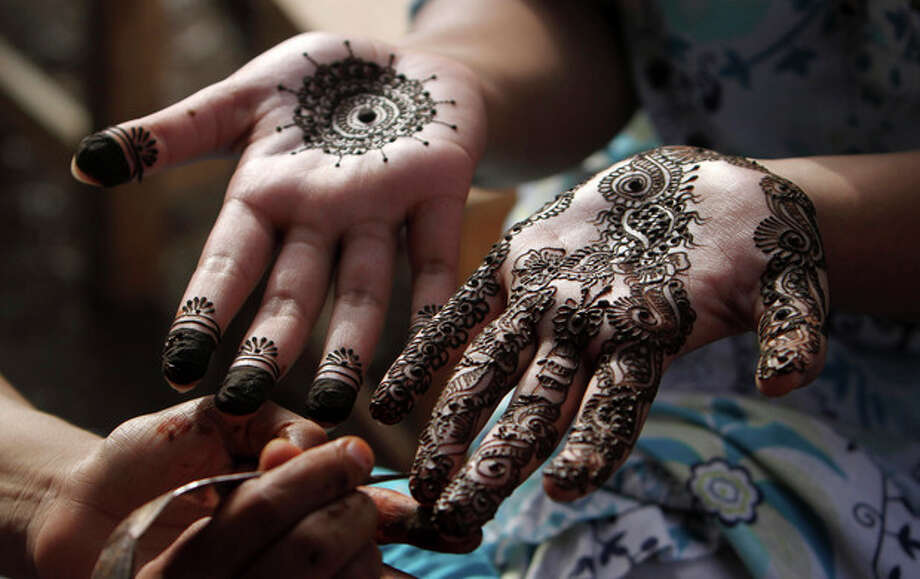 A Pakistani girl gets her hands painted with henna in preparation for the upcoming Eid al-Fitr festival, in Karachi, Pakistan, Saturday, Aug. 18, 2012. Eid al-Fitr marks the end of the holy month of Ramadan. (AP Photo/Fareed Khan) / AP
