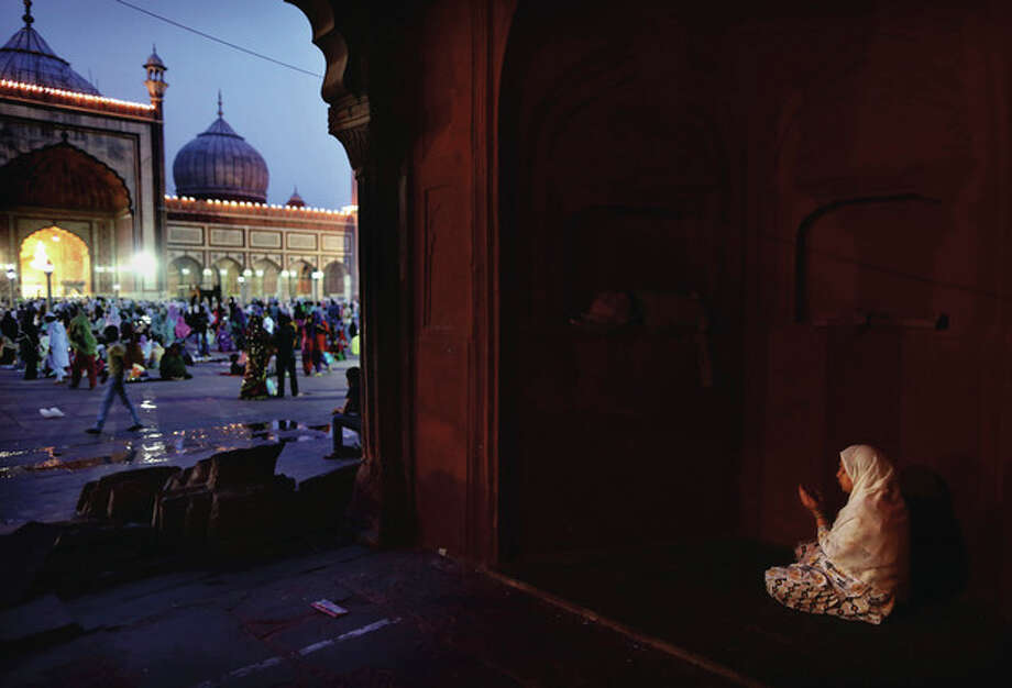 An Indian Muslim woman prays after breaking fast on the last day of the holy month of Ramadan before the Eid holiday, at the Jama Masjid in New Delhi, India, Sunday, Aug. 19, 2012. Muslims around the world celebrate Eid al-Fitr, marking the end of Ramadan, the Muslim calendar's ninth and holiest month. (AP Photo/Kevin Frayer) / AP