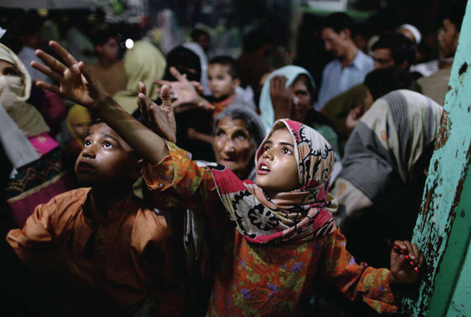 Pakistani women and children reach for donated food during the last Friday of the Muslim holy fasting month of Ramadan, at a restaurant in Rawalpindi, Pakistan, Friday, Aug. 17, 2012. For many years, Pakistan required all Sunni Muslims, who make up a majority of the country's population, to pay zakat to the government. That regulation changed recently, but many Pakistanis seem unaware and continue to pull their money out of the bank to elude the state. The food is donated by wealthy local Muslims who give money to local vendors to feed the poor during Islam's holiest month. (AP Photo/Muhammed Muheisen) / AP