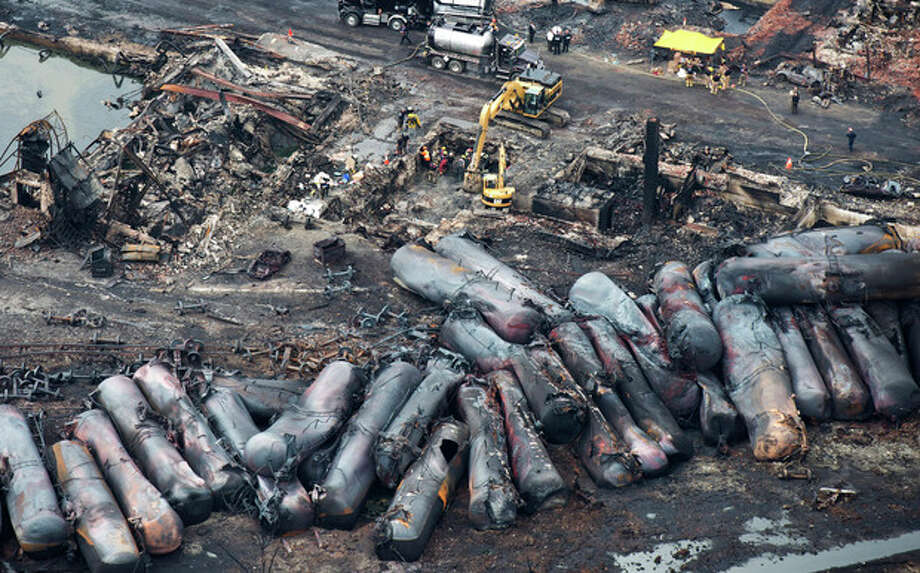 Workers comb through debris Tuesday, July 9, 2013, after a train derailed Saturday causing explosions of railway cars carrying crude oil in Lac-Megantic, Quebec. (AP Photo/The Canadian Press, Paul Chiasson) / The Canadian Press